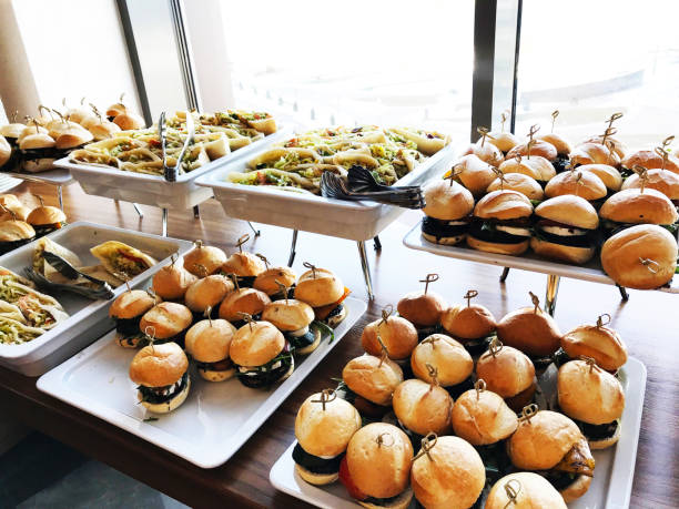 buffet table with small hamburgers, sandwiches and vegetables. catering service at the corporate business party or meeting - sideboard imagens e fotografias de stock