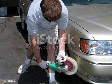 A man buff his car with a power buffer