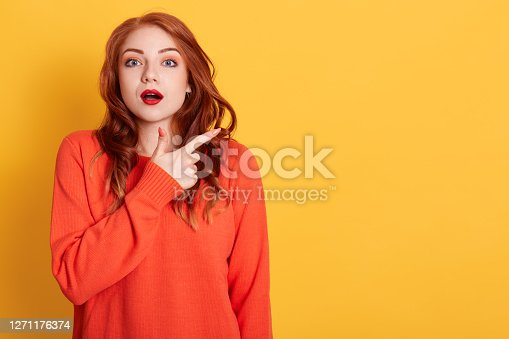 Bugged eyed beautiful red haired woman looks with astonished expression as advertises something unusual, indicates with fore finger aside at blank copy space.