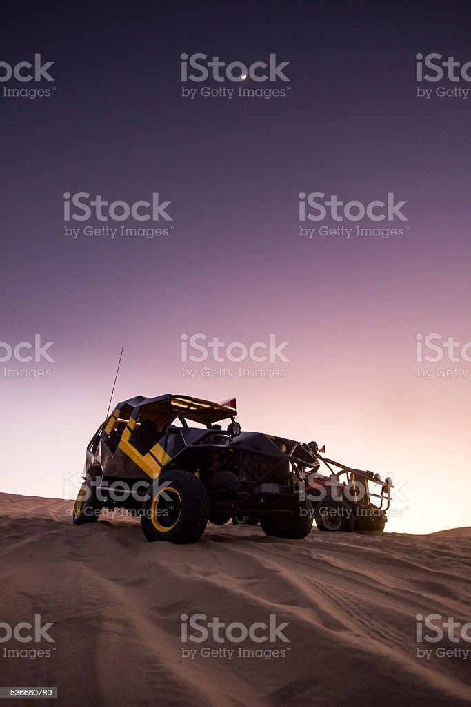 buggy on dunes at sunset stock photo