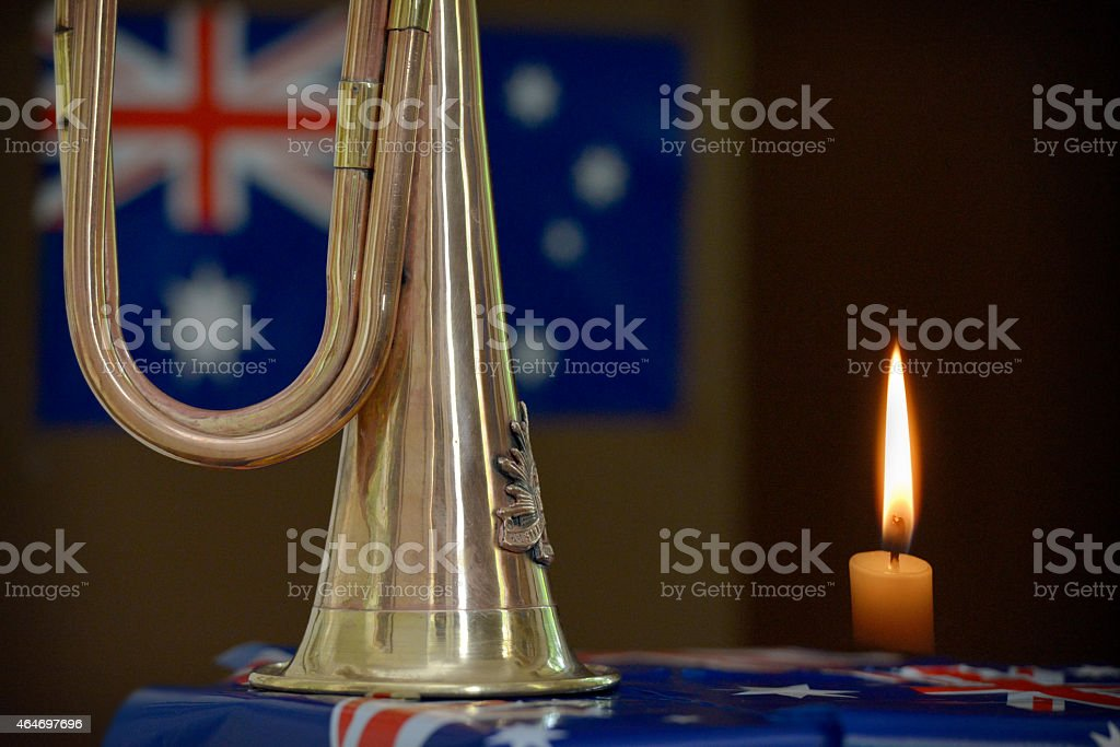 Bugle in front of an Australian flag with burning candle stock photo