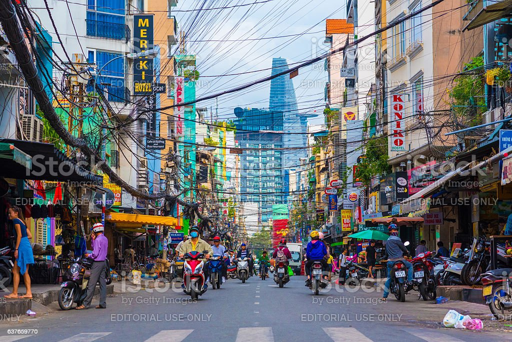 Bui Vien Street, Ho Chi Minh Ho Chi Minh, Vietnam - December 1, 2016: Bui Vien Street (a tourist area). Scooter traffic in Saigon tourist district with Bitexco Financial Tower in background. Many people (unidentified) walk and drive scooters. Many signboards of hotels and hostels. Asia Stock Photo