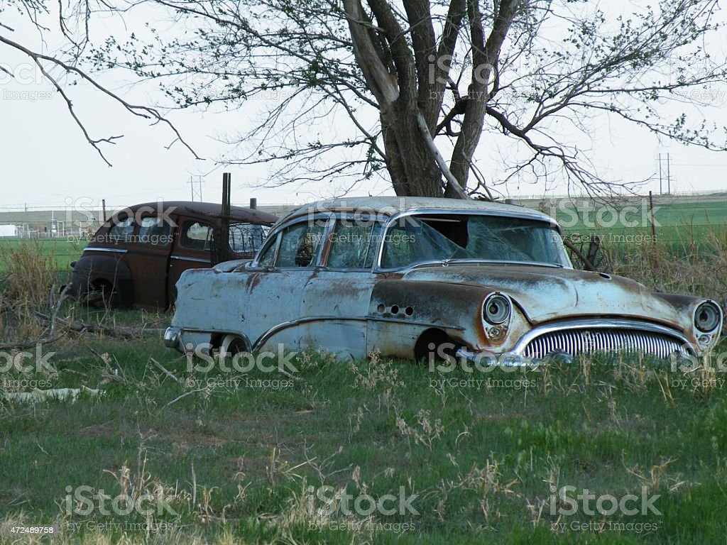 1954 Buick Roadmaster going to rust in a field stock photo