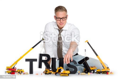 939533958 istock photo Build up trust: Businessman building trust-word. 162830748
