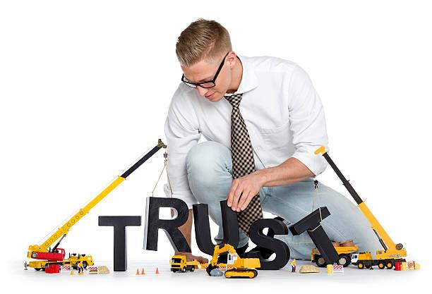 Build up trust: Businessman building trust-word. stock photo