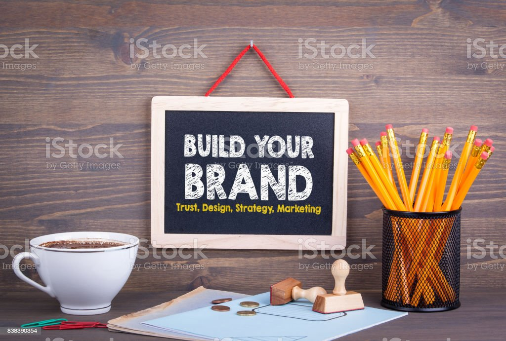 Build Your Brand concept. Trust Design Strategy Marketing. Chalkboard on a wooden background stock photo