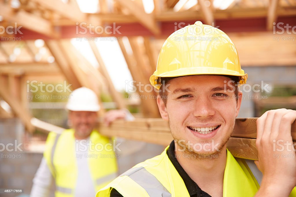 Builder And Apprentice Carrying Wood On Construction Site stock photo