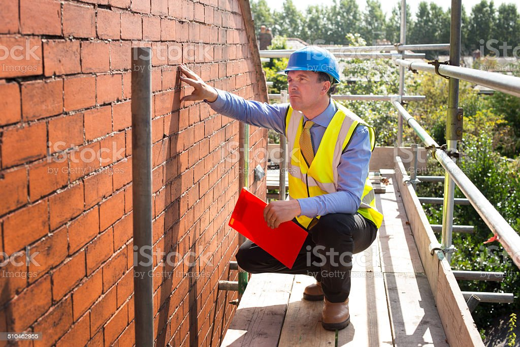 builder assesses brickwork on a gable end stock photo