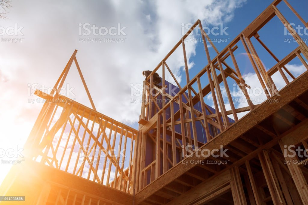 builder at work with wooden roof construction Wood Building frame stock photo
