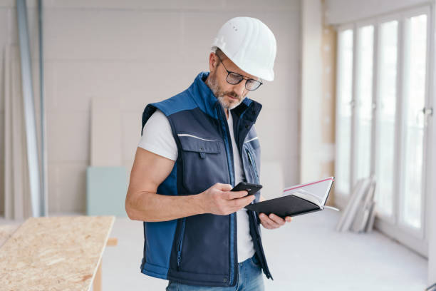 Builder checking a message on his mobile stock photo