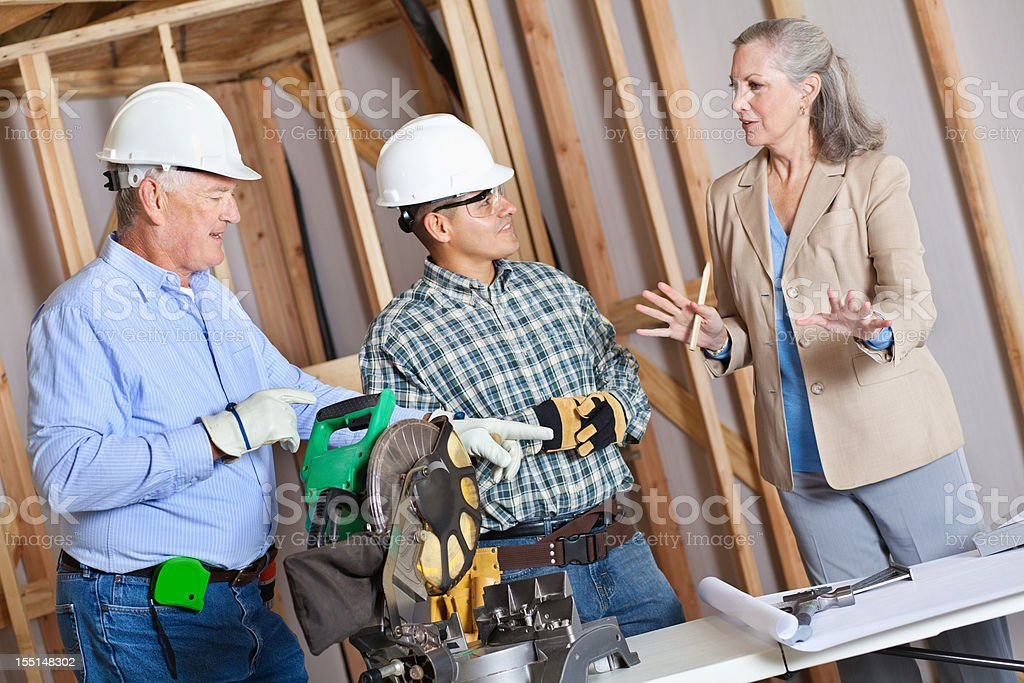 Builder explaining plans to construction team royalty-free stock photo