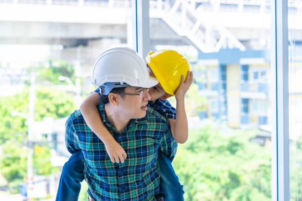 El padre constructor lleva a su hijo en su espalda por concepto de conexión padre hijo - foto de stock
