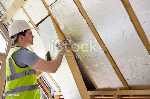 466705128 istock photo Builder Fitting Insulation Into Roof Of New Home 501959963