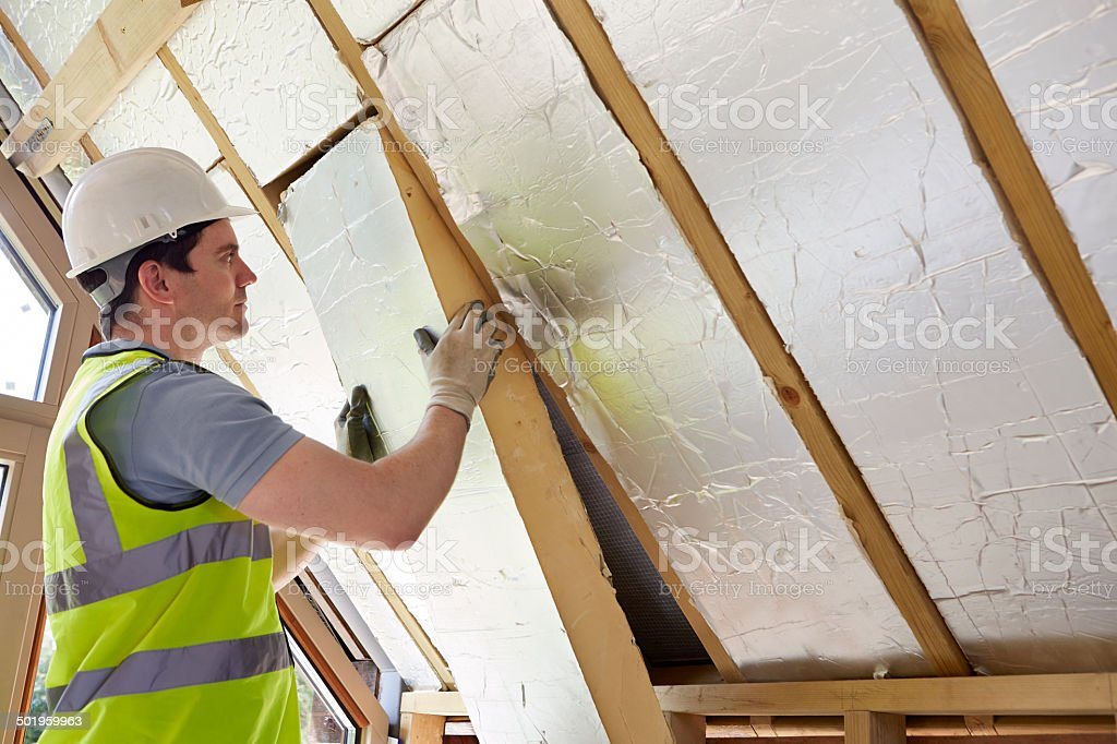 Builder Fitting Insulation Into Roof Of New Home stock photo