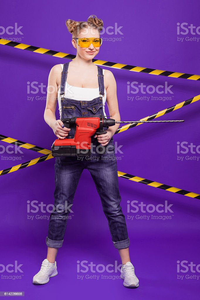 Builder girl  with a professional building tool stock photo