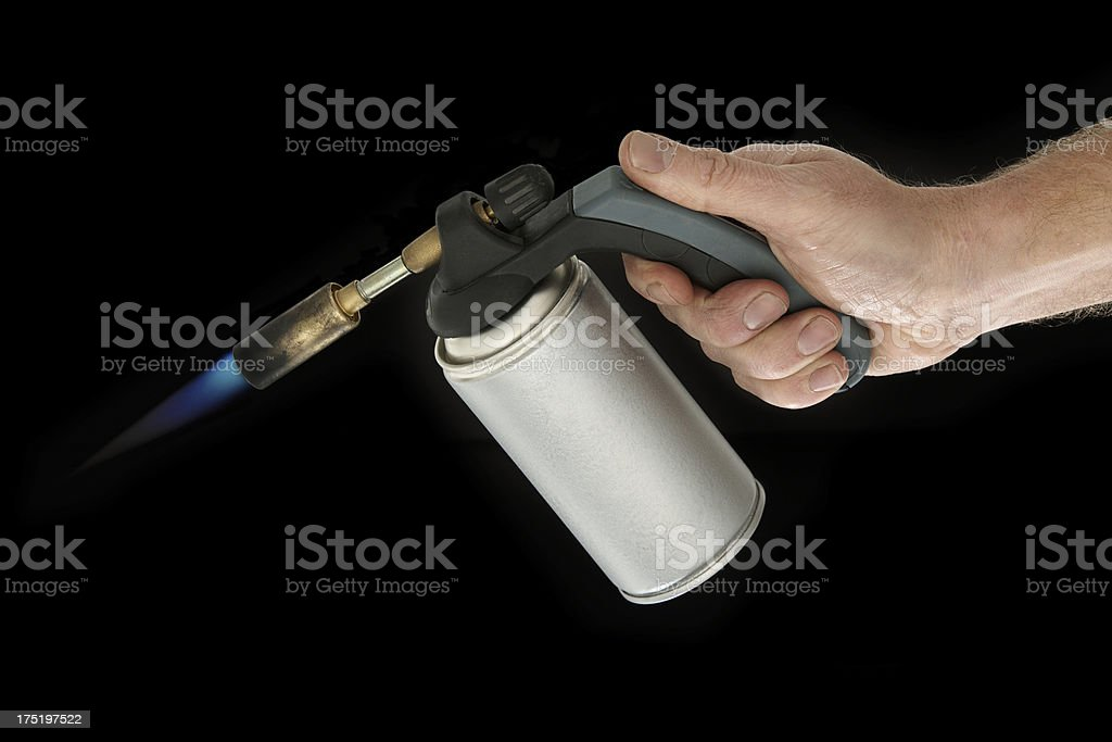 Builder hand holding blow torch on black background stock photo