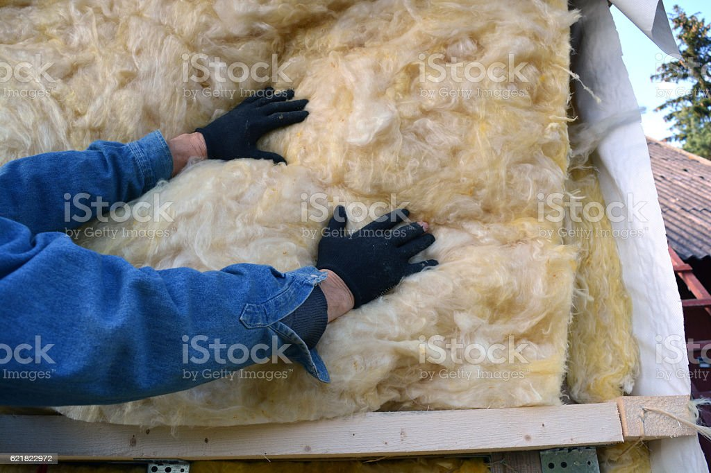Builder hands insulating wooden house with mineral  wool stock photo