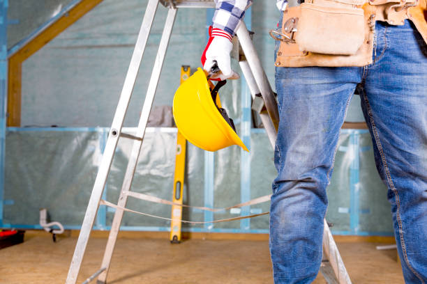 Builder handyman with yellow safety helmet and tool belt on attic renovation site stock photo
