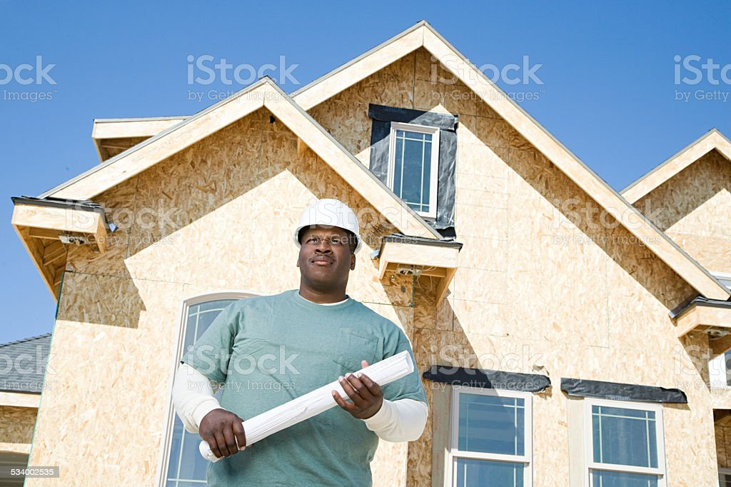 Builder holding a blueprint stock photo