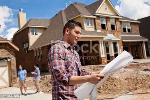 istock Builder in foreground with buyers background at new home construction 171302585