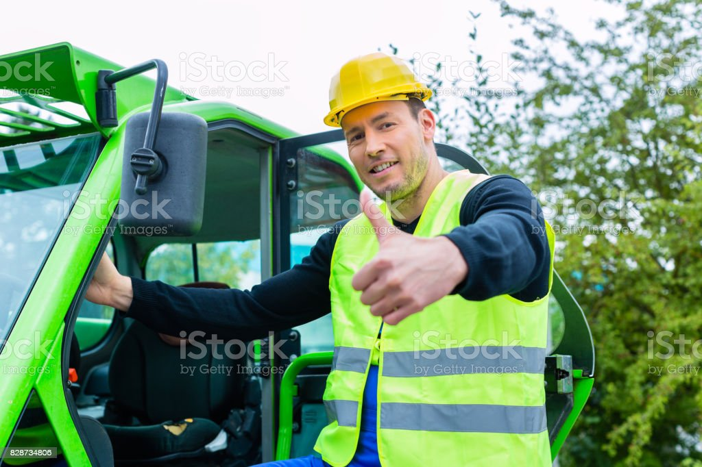 Builder in front of  construction machinery stock photo