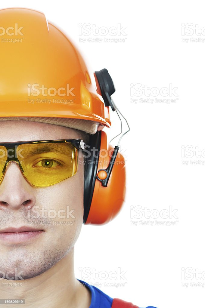 builder in hard hat, earmuffs and goggles stock photo