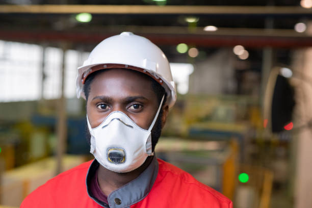 Builder in respirator and hardhat stock photo