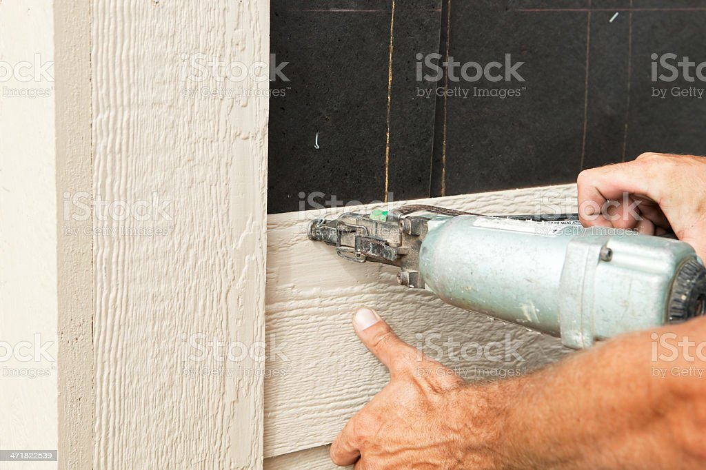 Builder Installing House Siding onto Tar Paper Covered Wall royalty-free stock photo