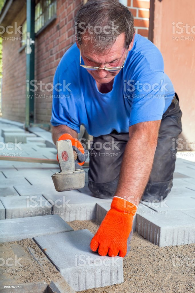 Builder laying a new patio floor at a house. stock photo