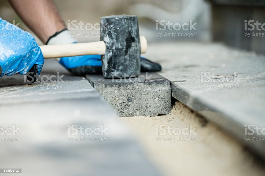 Builder laying a paving stone or brick stock photo