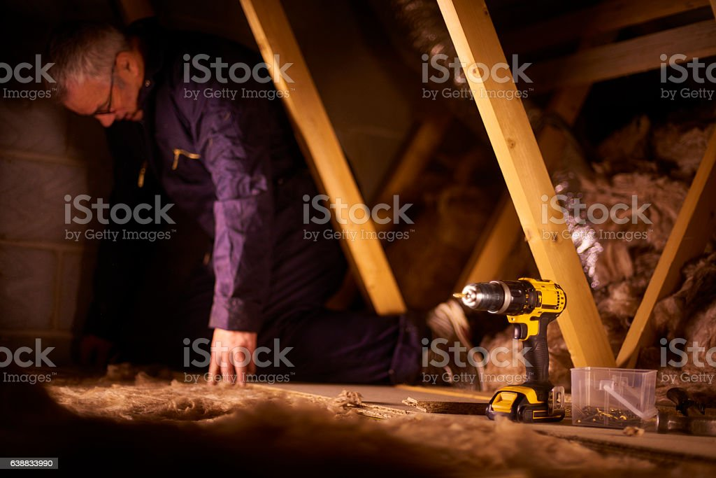 builder laying attic flooorbaord stock photo