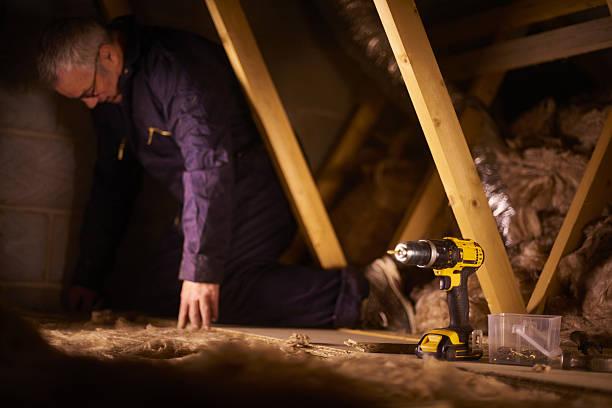 builder laying attic flooorbaord stock photo