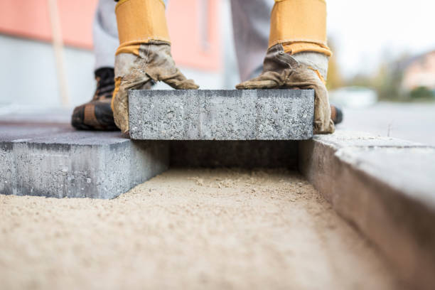 Builder laying outdoor paving slabs stock photo