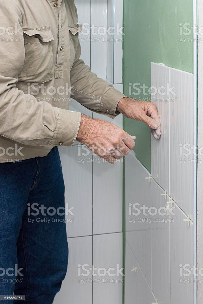 Builder laying tiles in shower recess stock photo
