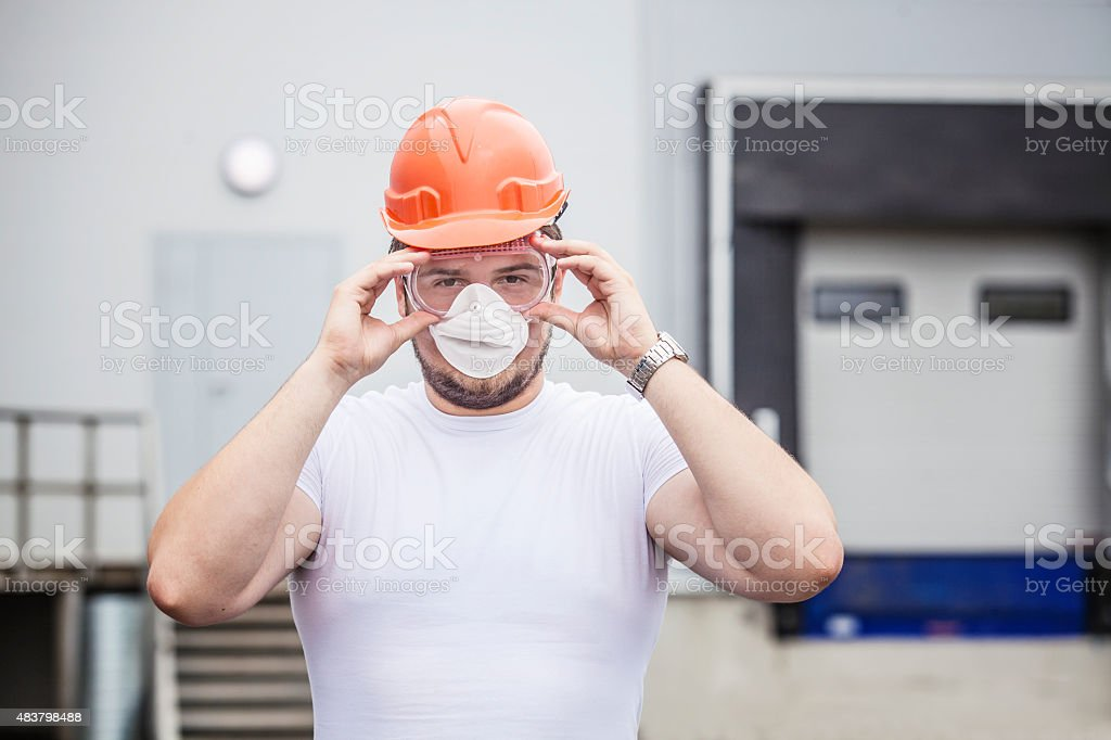 Builder male worker in protective mask and glasses stock photo