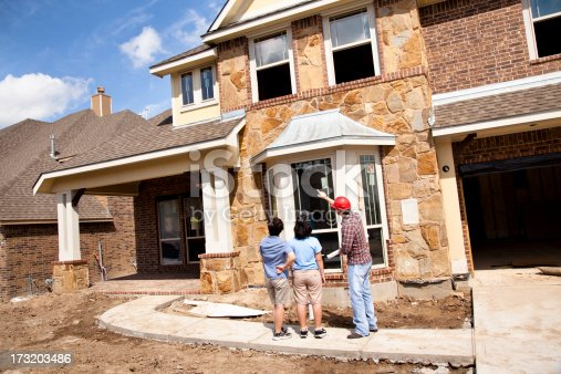 istock Builder meeting with woman and daughter at new home construction 173203486