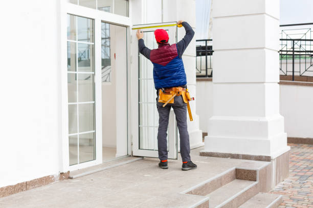 Builder mounting electric wiring on the building facade for outdoor lighting stock photo
