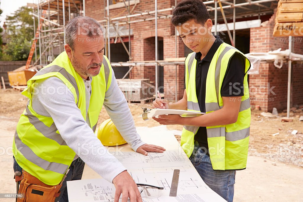 Builder On Building Site Discussing Work With Apprentice stock photo