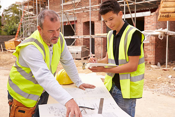Builder sur chantier discuter de travailler avec d'apprentissage - Photo