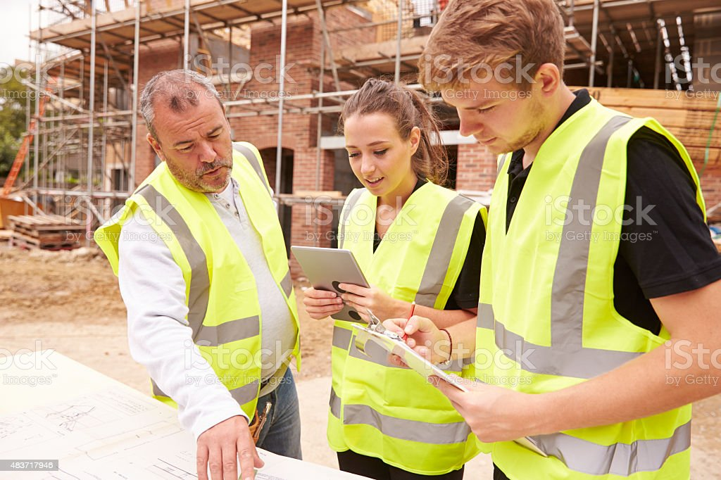 Builder On Building Site Discussing Work With Apprentices stock photo
