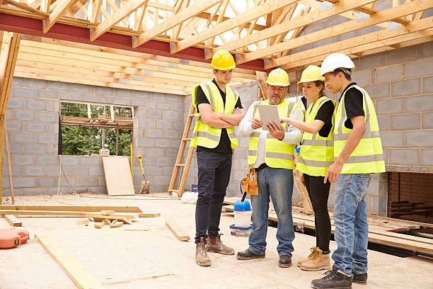 Builder On Site Looking At Digital Tablet With Apprentices stock photo