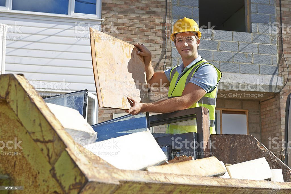 Builder Putting Waste Into Rubbish Skip royalty-free stock photo