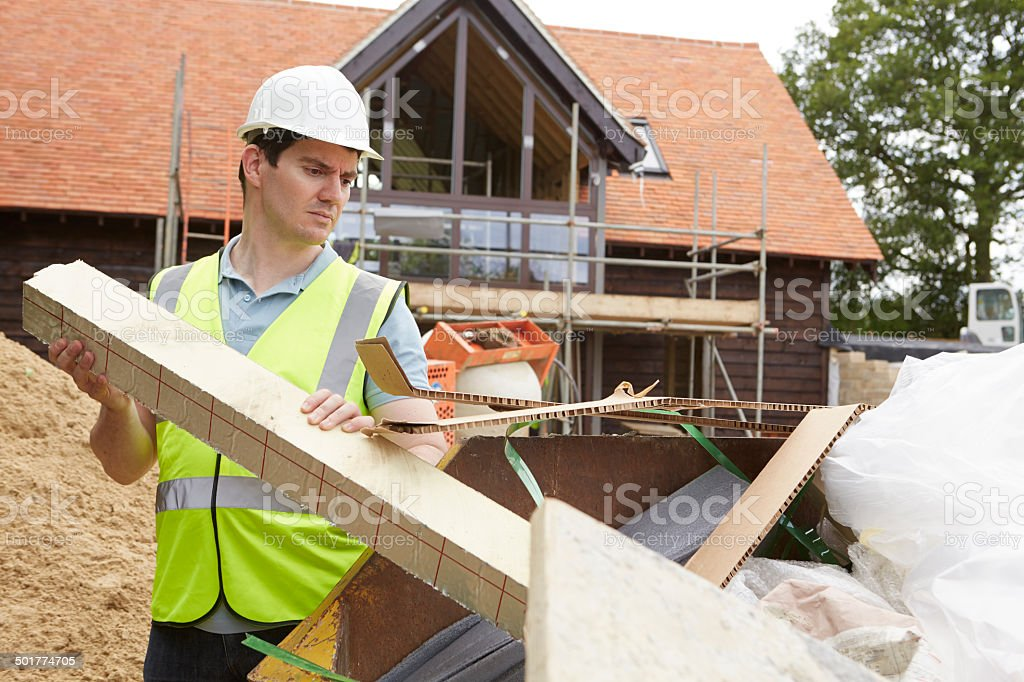 Builder Putting Waste Into Rubbish Skip stock photo