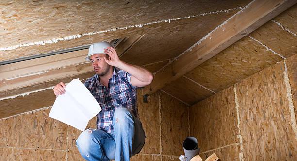 builder reading plans inside unfinished home - kruipruimte stockfoto's en -beelden