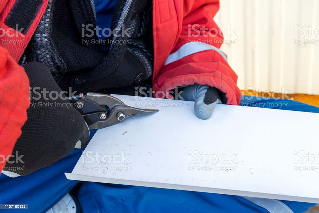 Builder scissors cuts a steel sheet. Worker tin cuts out the iron...