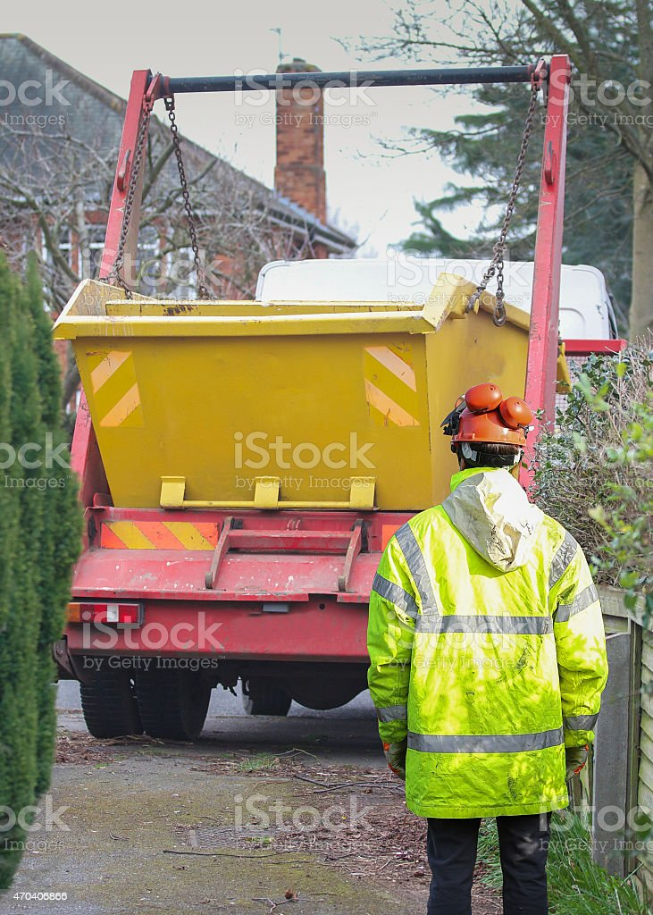Builder supervising the delivery and unloading of a skip stock photo