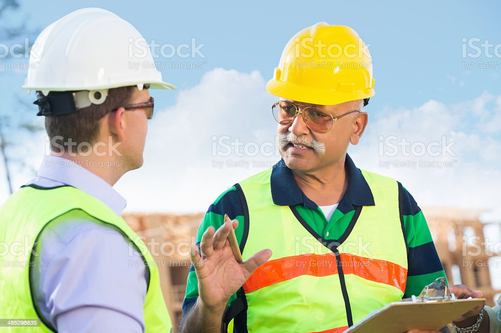 Builder talking to co-worker about construction plans royalty-free stock photo