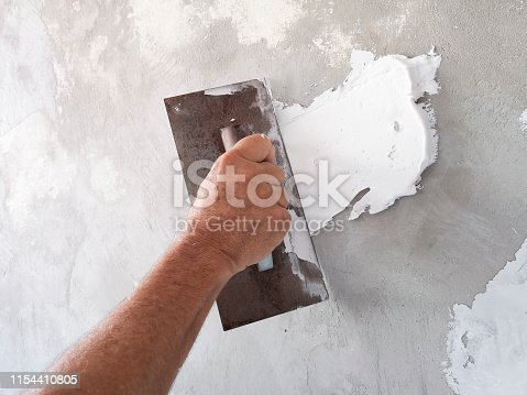 istock Builder using plastering tool for finishing old wall. 1154410805