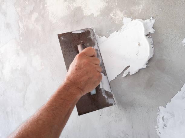 constructor con herramienta de enyesado para terminar la pared vieja. - estuco fotografías e imágenes de stock