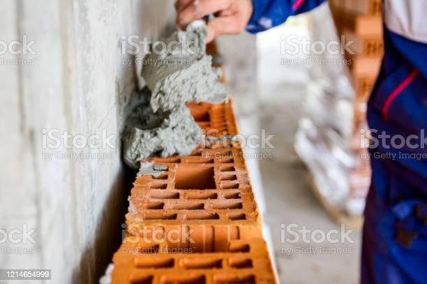 Builder using spatula to set up mortar over red brick picture id1214654999?b=1&k=6&m=1214654999&s=612x612&h=zvpf7guouabaumquealjalnbfwfsr ffaicovdpf7gy=